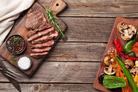 Photo pour Beef steak and grilled vegetables on cutting board on wooden table. Top view with copy space - image libre de droit
