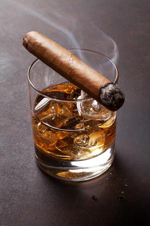 Foto de Whiskey with ice and cigar on dark stone table - Imagen libre de derechos