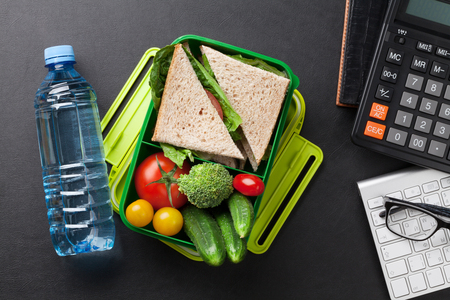 Photo for Office desk with supplies and lunch box with vegetables and sandwich. Top view - Royalty Free Image