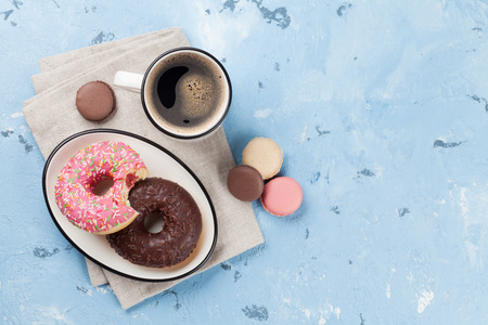 Photo for Coffee cup and colorful donuts on stone table. Top view with copy space - Royalty Free Image