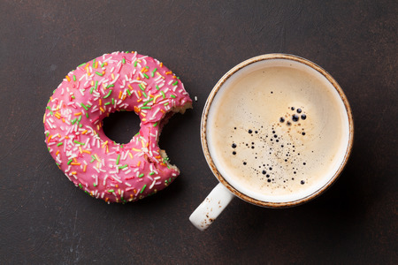 Photo for Coffee cup and pink donut on stone table. Top view - Royalty Free Image