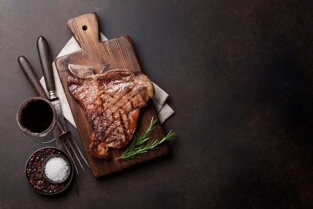 Foto de Grilled T-bone steak and red wine glass on stone table. Top view with copy space - Imagen libre de derechos