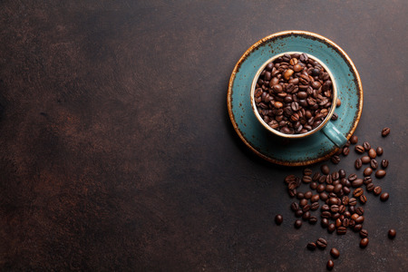 Foto de Coffee cup with roasted beans on stone background. Top view with copy space for your text - Imagen libre de derechos