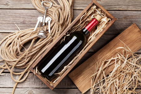 Foto de Red wine bottle in box on wooden table. Top view - Imagen libre de derechos