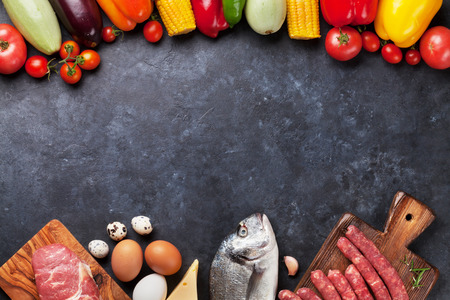Foto de Vegetables, fish, meat and ingredients cooking. Tomatoes, eggplants, corn, beef, eggs, cheese. Top view with copy space on stone table - Imagen libre de derechos
