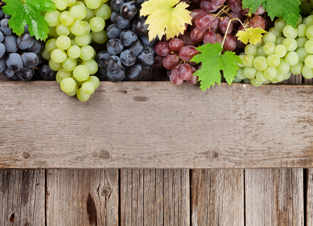 Photo pour Various colorful grapes on wooden background. With space for your text - image libre de droit