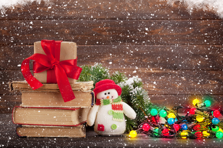 Foto de Christmas greeting card with gift box, snowman toy and colorful lights in front of wooden wall. With space for your greetings - Imagen libre de derechos