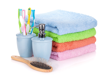 Photo pour Four toothbrushes, liquid soap, hairbrush and colorful towels. Isolated on white background - image libre de droit