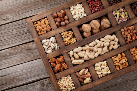 Photo for Various nuts selection: peanuts, hazelnuts, chestnuts, walnuts, pistachio and pecans in wooden box. Top view with space for your text - Royalty Free Image