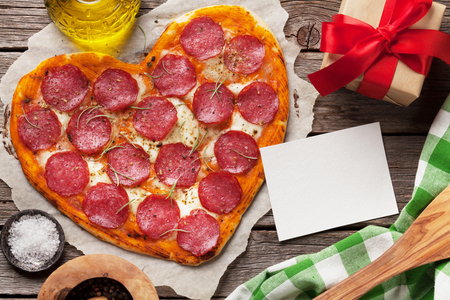 Foto de Heart shaped pizza with pepperoni and mozzarella. Valentines day greeting card. Top view with space for your text - Imagen libre de derechos