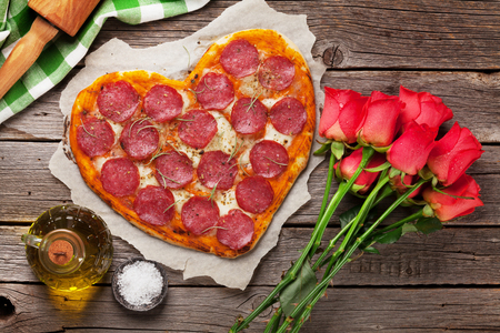 Foto per Heart shaped pizza with pepperoni and mozzarella and red rose flowers bouquet. Valentines day greeting card. - Immagine Royalty Free