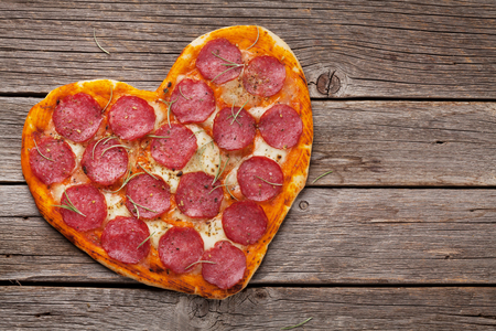 Photo pour Heart shaped pizza with pepperoni and mozzarella. Valentines day greeting card. Top view - image libre de droit