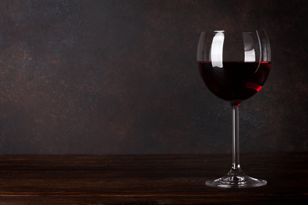 Foto de Red wine glass in front of blackboard wall. With copy space for your text - Imagen libre de derechos