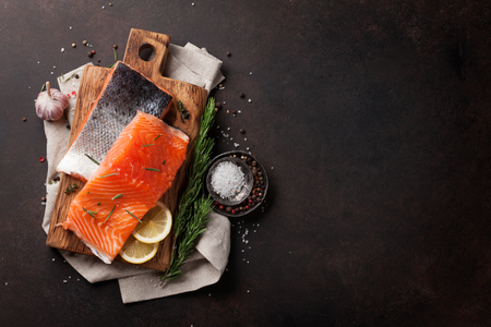 Foto de Raw salmon fish fillet with spices cooking on stone table. Top view with space for your text - Imagen libre de derechos