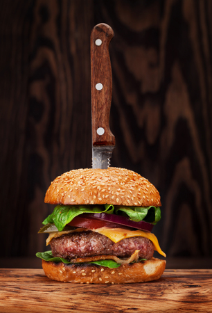 Foto de Tasty grilled home made burger with beef, tomato, cheese, cucumber and lettuce - Imagen libre de derechos
