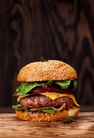 Photo pour Tasty grilled home made burger with beef, tomato, cheese, cucumber and lettuce. With copy space - image libre de droit