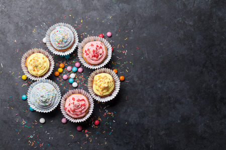 Photo pour Sweet cupcakes with colorful decor and candies. Top view with space for your greetings - image libre de droit