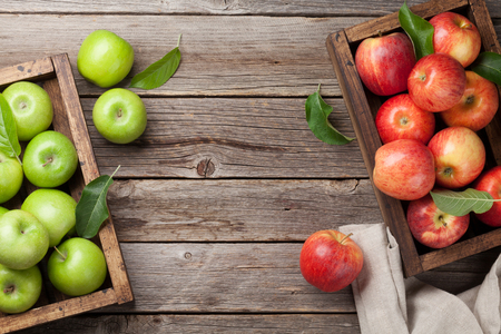 Foto de Ripe green and red apples in wooden box. Top view with space for your text - Imagen libre de derechos