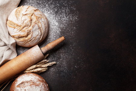 Photo for Homemade crusty bread cooking on stone table. Top view with space for your text - Royalty Free Image