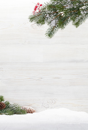 Photo pour Christmas backdrop with fir tree branch covered by snow in front of wooden wall. Xmas background with space for your greetings - image libre de droit