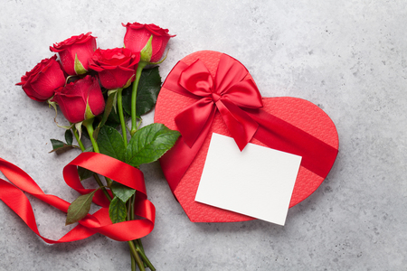 Photo pour Valentine's day greeting card with red rose flowers bouquet and gift box on stone background. Top view with space for your greetings - image libre de droit