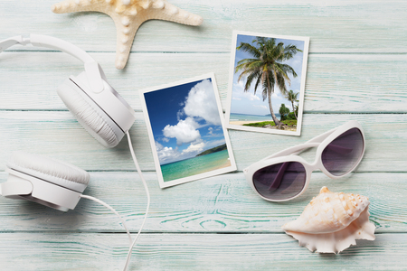 Photo pour Travel vacation background concept with sunglasses, headphones and weekend photos on wooden backdrop. Top view. - image libre de droit
