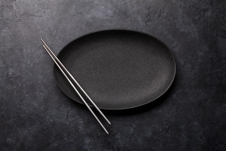 Foto de Empty plate and chopsticks over black textured table. Japanese food template. Top view with copy space. Flat lay - Imagen libre de derechos