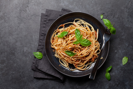 Photo pour Spaghetti bolognese pasta with tomato and minced meat sauce, parmesan cheese and fresh basil. Top view with copy space - image libre de droit