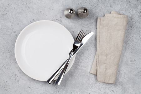 Foto de Table setting. Empty plate, knife, fork, spices and napkin. Top view and flat lay with copy space - Imagen libre de derechos