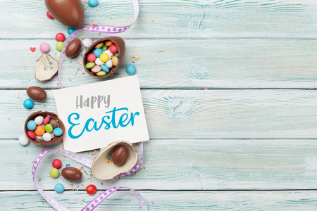 Photo for Easter greeting card with chocolate eggs and colorful candies. Top view on wooden table with space for your greetings - Royalty Free Image