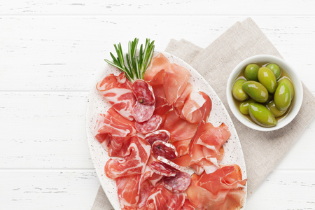 Photo pour Traditional spanish jamon, prosciutto crudo, italian salami, parma ham. Antipasto plate and olives. Top view flat lay. With copy space - image libre de droit
