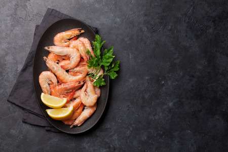 Foto de Steamed tiger shrimps with parsley and lemon. Top view with copy space for your text - Imagen libre de derechos