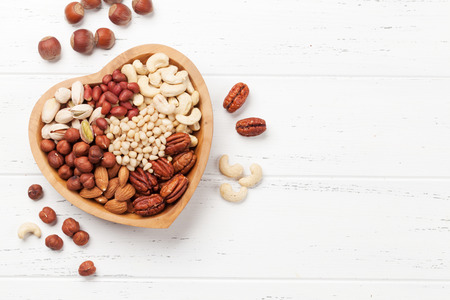 Foto de Various nuts selection: peanuts, hazelnuts, chestnuts, walnuts, pistachio and pecans on wooden table. Top view with space for your text - Imagen libre de derechos