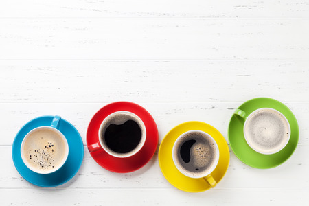 Photo pour Colorful coffee cups on white wooden table. Top view flat lay with copy space - image libre de droit