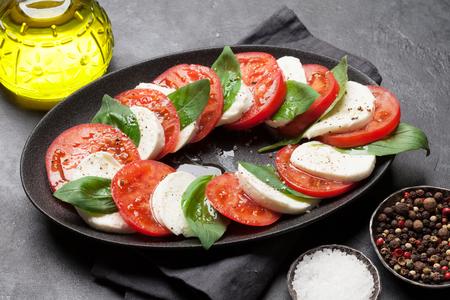 Foto per Delicious italian caprese salad with ripe tomatoes, fresh garden basil and mozzarella cheese - Immagine Royalty Free