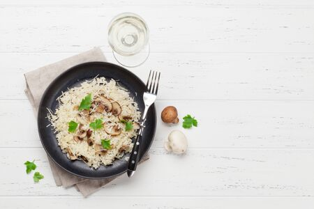 Foto de Delicious mushrooms risotto dressed with parmesan cheese and parsley. With white wine glass. Top view with copy space - Imagen libre de derechos