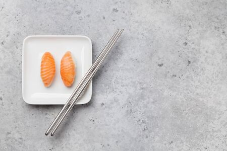 Photo pour Japanese sushi set with salmon. Sake. Sashimi, maki rolls. On plate over stone background with space for your text - image libre de droit