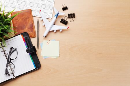Photo pour Business trip concept. Accessories on desk table. Pc keyboard, passport, notepad, calendar and airplane toy. Top view with copy space - image libre de droit