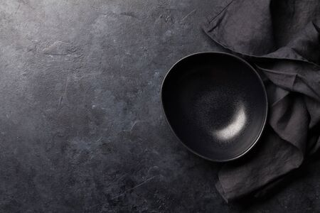 Photo pour Kitchen table with empty plate and towel. Cooking stone backdrop. Top view with copy space. Flat lay - image libre de droit