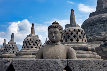 Photo for Borobodur ancient heritage of buddhism, Buddha statue and bell-shaped stupas on the main stupa of Borobudur, with blue cloudy sky / Borobodur ancient heritage of buddhism - Royalty Free Image
