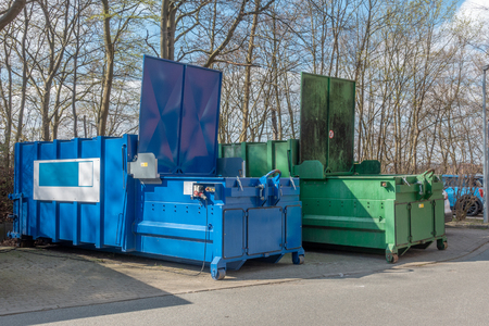 Photo for two large garbage compactors standing on a hospital site - Royalty Free Image