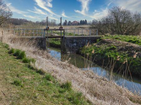 Foto de n old water lock serves to dam the water of a small river - Imagen libre de derechos