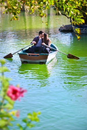 Foto de Romantic young couple boating on calm lake   - Imagen libre de derechos