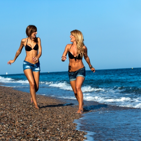 Photo pour Attractive two young girl friends running along seside   - image libre de droit