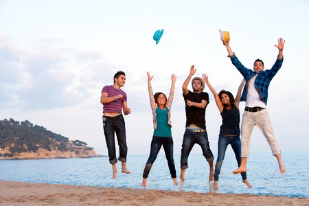 Photo for Group of energetic friends jumping high on beach  - Royalty Free Image