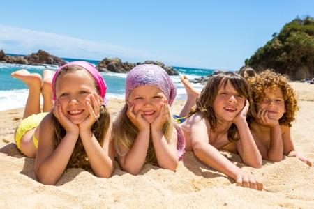 Foto de Portrait of children laying on sand at beach  - Imagen libre de derechos