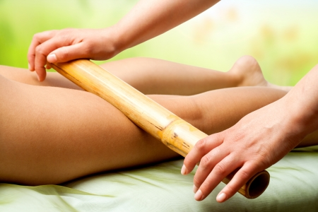 Photo for Close up of therapist hands massaging female legs with bamboo stick. - Royalty Free Image