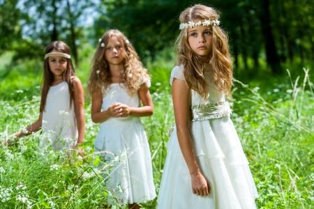 Photo pour Portrait of three girl friends wearing white dresses in woods. - image libre de droit