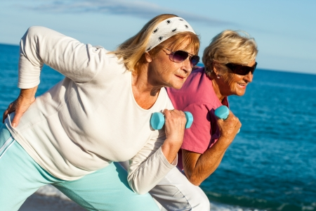 Photo pour Two elderly fitness girlfriends working out together on beach. - image libre de droit