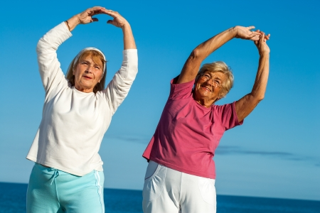 Photo pour Portrait of two senior fitness ladies stretching arms outdoors. - image libre de droit